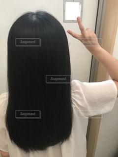 女性の後ろ姿でピースサインの写真・画像素材[1275919]