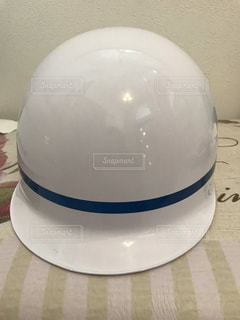 テーブルの上の白いヘルメットの写真・画像素材[1566404]