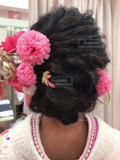 ピンクの花を身に着けている女性の写真・画像素材[1718733]
