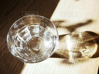 陽射しを受けて光るテーブルの上の水の写真・画像素材[4168706]