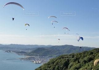 水域で凧を飛ばす人々のグループの写真・画像素材[2711130]