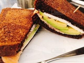 黒パンのサーモンとアボカドのサンドイッチの写真・画像素材[3347221]