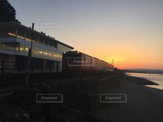 夕焼けをバックに走る電車の写真・画像素材[1272256]