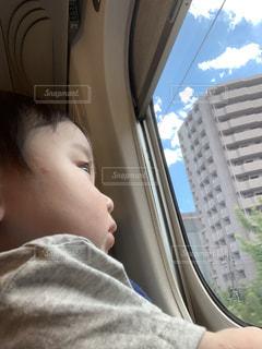 窓から世界を見る子供の写真・画像素材[2434778]