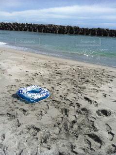 砂浜の上に座っている青い浮輪の写真・画像素材[1274855]