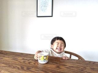 木製のテーブルの上に座っている小さな女の子の写真・画像素材[2683552]