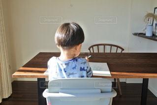 テーブルに座っている小さな男の子の写真・画像素材[2683553]