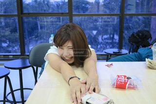 窓の前のテーブルに座っている女性の写真・画像素材[1278591]