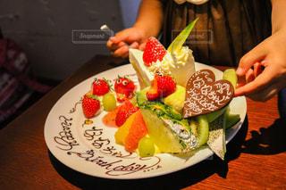テーブルに食べ物のプレートを持っている人の写真・画像素材[1278989]