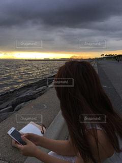 海岸沿いに座っている女性の写真・画像素材[1279854]