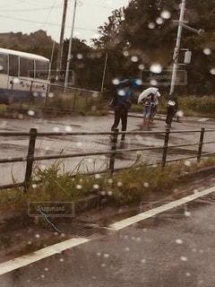 雨の中で立っている人の写真・画像素材[1280981]
