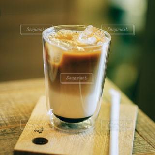 近くの木製のテーブルの上のガラスのコップで飲み物をの写真・画像素材[1283823]