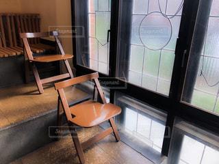 窓の前に座っている椅子の写真・画像素材[1303834]