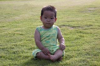 芝生に座っている小さな男の子の写真・画像素材[1859947]