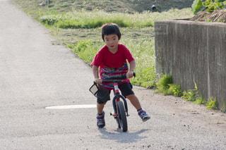 未舗装の道路を自転車に乗る少年の写真・画像素材[1920813]