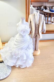 テーブルの上のミニドレスとタキシードの写真・画像素材[1302920]
