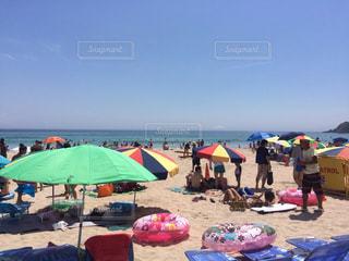 砂のビーチ パラソルに座っている人々 のグループの写真・画像素材[1294315]