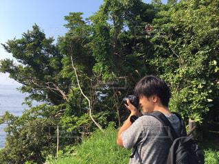 ツリーの前に立っている男の写真・画像素材[1295558]