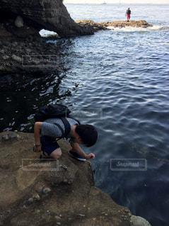水の体の横にある岩の上に座っている男の写真・画像素材[1295559]