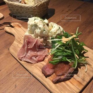 木製のテーブルの上に食べ物の写真・画像素材[1295561]
