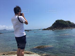 水の体の近くのビーチに立っている人の写真・画像素材[1295687]