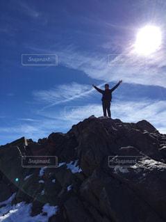 岩が多い丘の上に立っている人の写真・画像素材[1299189]