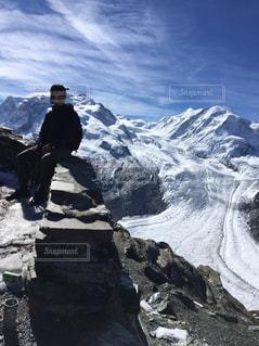 雪に覆われた山の頂上に立っている男の写真・画像素材[1299190]