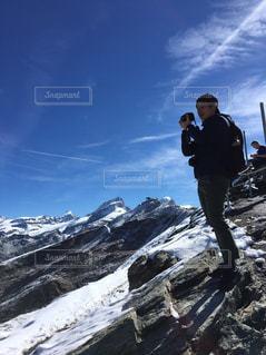 雪に覆われた山の頂上に立っている男の写真・画像素材[1299193]