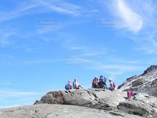岩が多い丘の上に空気を通って飛んで男の写真・画像素材[1299562]