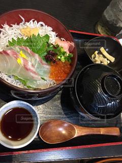 テーブルの上の皿の上に食べ物のボウルの写真・画像素材[1296033]