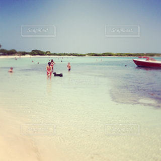 水の体の近くのビーチの人々 のグループの写真・画像素材[1313085]
