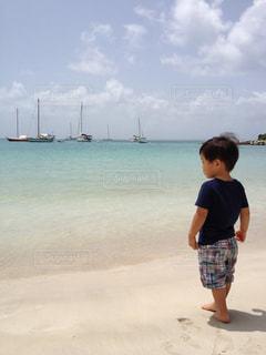 砂浜に立っている少年の写真・画像素材[1319767]