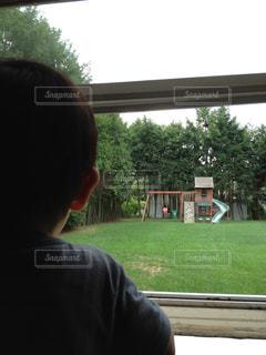 窓から外を眺める少年の写真・画像素材[1328084]
