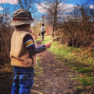 草の中に立っている小さな男の子の写真・画像素材[1328533]