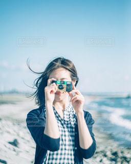 海で写真を撮っている女の人の写真・画像素材[1297053]