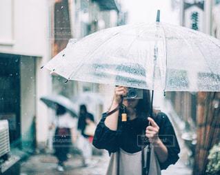 傘を持って雨の中を歩く女性の写真・画像素材[1297924]