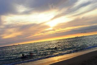 海の横にあるビーチに沈む夕日の写真・画像素材[1353890]