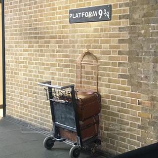 れんが造りの建物の側に座って荷物のバッグの写真・画像素材[1713733]