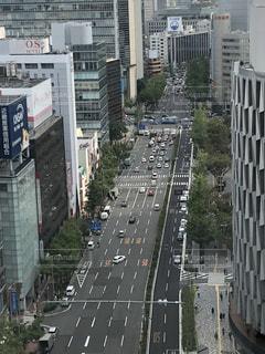 背の高い建物に囲まれたトラフィックでいっぱいの都市通りの写真・画像素材[1552500]