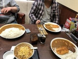 食品のプレートをテーブルに座っている男の人の写真・画像素材[1297132]