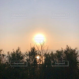背景に夕日のある人の写真・画像素材[4137368]