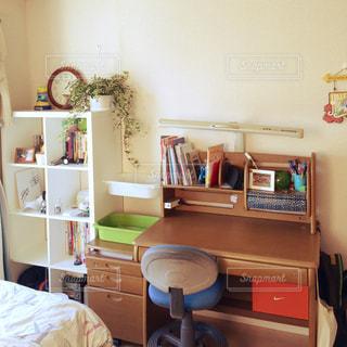 ベッドと小さな部屋で机付きのベッドルームの写真・画像素材[1301822]