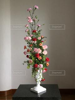 テーブルの上に座っての花で一杯の花瓶の写真・画像素材[1308795]