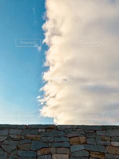 レンガの壁の向こうの雲の写真・画像素材[1376010]