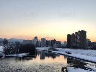 夕焼けが映る川と街の景色の写真・画像素材[1821179]