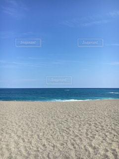 海の横にある砂浜のビーチの上に立っている人の写真・画像素材[1309648]