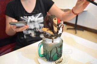 テーブルの上のケーキを持っている人の写真・画像素材[1310355]