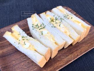 木製のまな板の上にパンの切れ端の写真・画像素材[1585410]