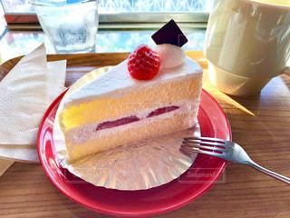 木製テーブルの上に座っているケーキのスライスの写真・画像素材[1623154]