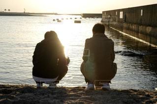 水の体の横に立っている人の写真・画像素材[1695600]